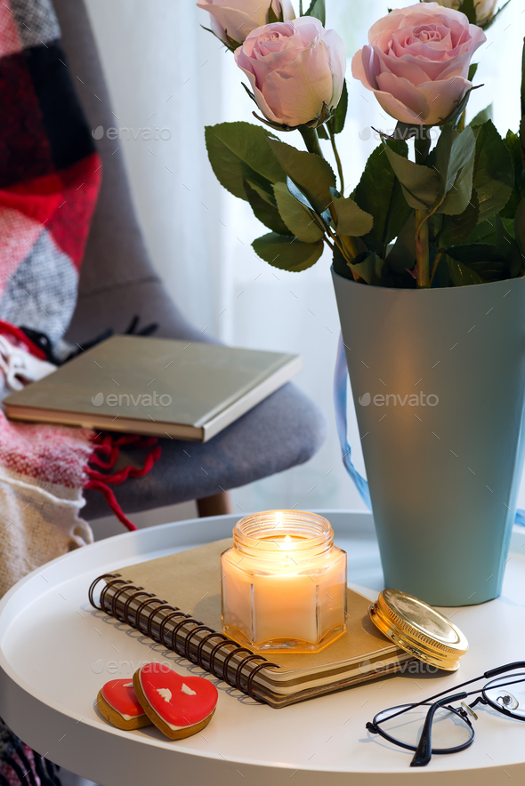 A candle with a notebook on a table with pink roses in a box near a window with a tool, a plaid and - Stock Photo - Images