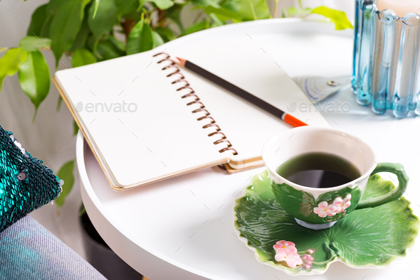 a cup of herbal tea on a table with notepad and candle . Bedroom interior - Stock Photo - Images