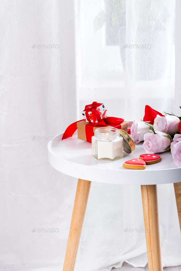 Homemade Valentines day heart cookies, pink roses and candle on white table over window, copy space - Stock Photo - Images