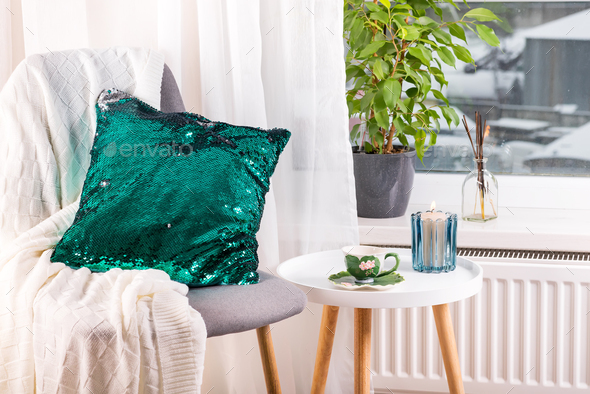 a cup of herbal tea on a table, a knitted wool blanket , green sequin pillow on a chair and candle - Stock Photo - Images