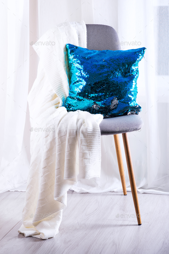 White plaid and blue sequins pillow on gray armchair over window of living room - Stock Photo - Images