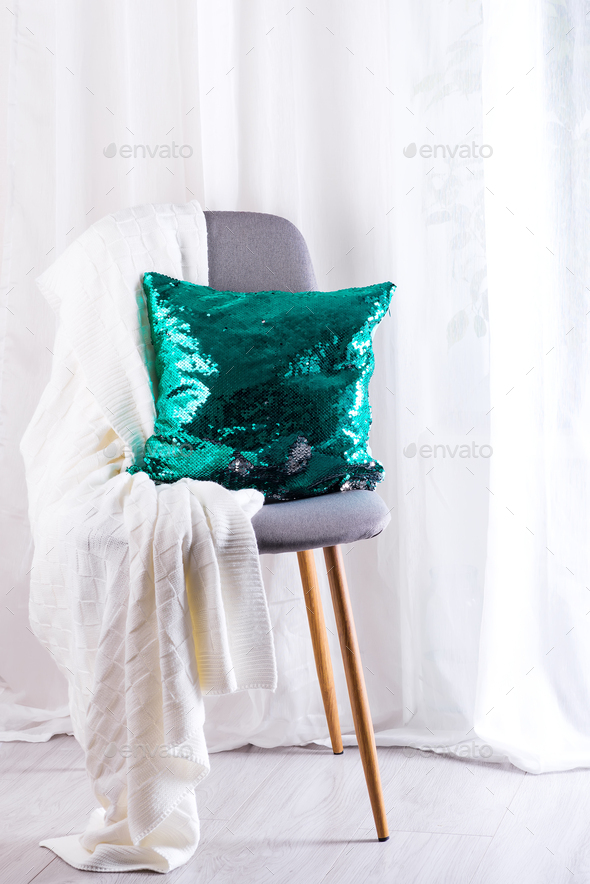 White plaid and green sequins pillow on gray armchair over window of living room - Stock Photo - Images