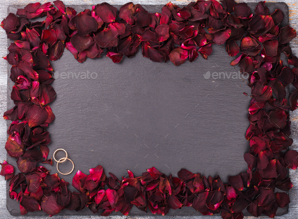 Background of red rose petals and wedding rings. - Stock Photo - Images