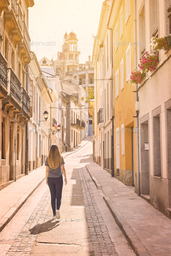Young woman walking by the streets of Ribadeo, Galicia - Stock Photo - Images