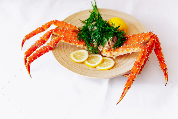 Red king crab on a plate with lemon and dill. White background - Stock Photo - Images