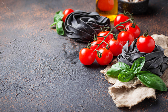 Black uncooked pasta with tomato and basil - Stock Photo - Images