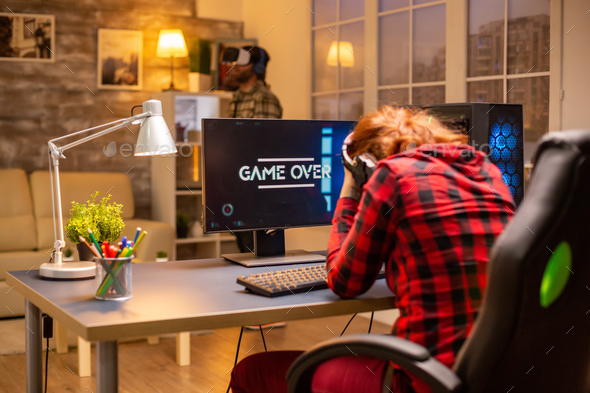 Gamer woman losing at a video game playing late at night in the living room - Stock Photo - Images