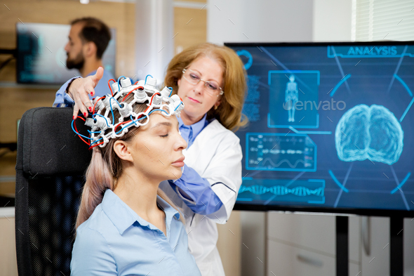 Doctor arranging neurology scanning headset for tests on a female patient - Stock Photo - Images