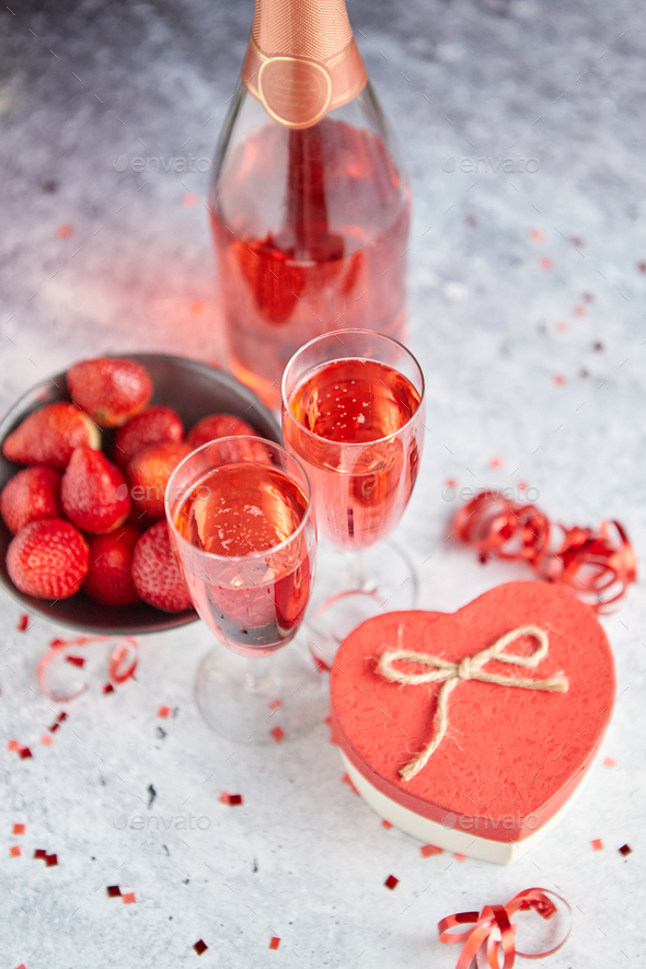 Bottle of rose champagne, glasses with fresh strawberries and heart shaped gift - Stock Photo - Images