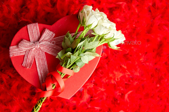 Heart shaped boxed gift, placed on red feathers background - Stock Photo - Images