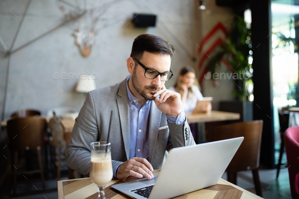 Portrait of a successful business man sitting at the cafe in front of a laptop - Stock Photo - Images
