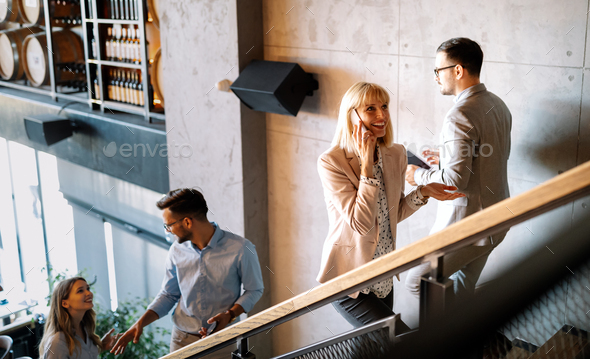Busy business people on stairs in modern office - Stock Photo - Images