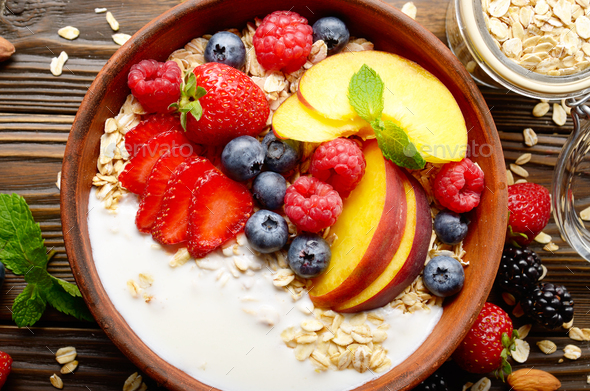 Flat lay of fruit healthy muesli with peaches strawberry almonds and blackberry - Stock Photo - Images