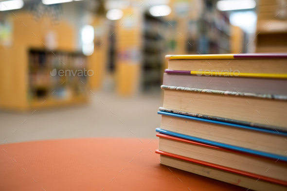 Stack of books on a wooden table in a library - Stock Photo - Images