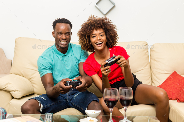 Black African American couple having fun playing video games - Stock Photo - Images