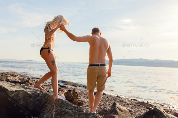 Romantic Man Holding Hand Helping Girlfriend On Rocks - Stock Photo - Images