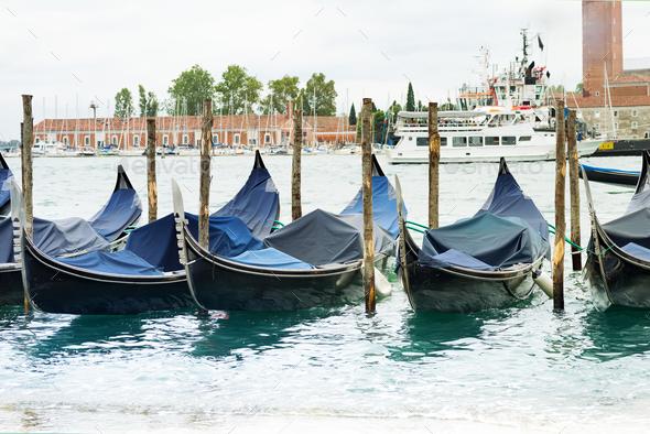 Gondolas moored by Saint Mark square with San Giorgio di Maggiore church in Venice, Italy - Stock Photo - Images
