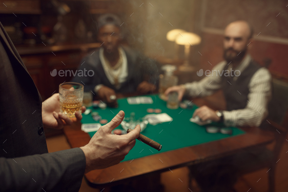 Three poker players sitting at the table, casino - Stock Photo - Images