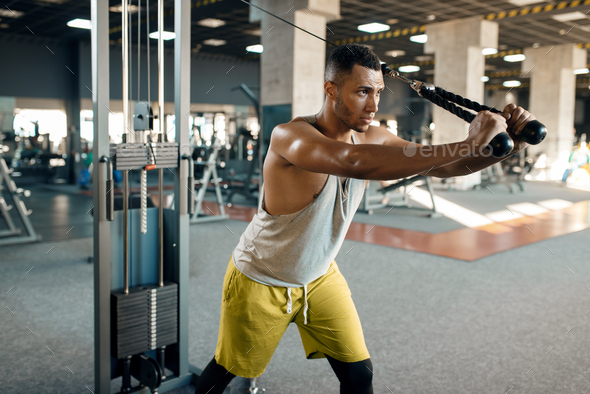 Athlete at exercise machine in motion, sport club - Stock Photo - Images