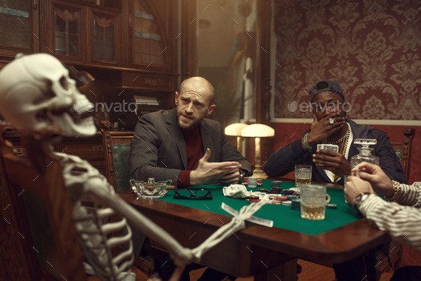 Poker players and skeleton at gaming table, fun - Stock Photo - Images