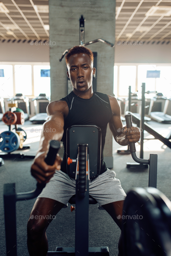 Muscular sportsman at exercise machine in gym - Stock Photo - Images