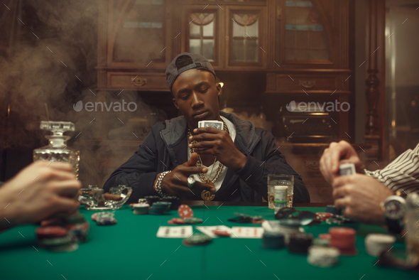 Poker players at gaming table with bets, casino - Stock Photo - Images