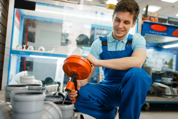 Sanitary technician with pipe wrench at showcase - Stock Photo - Images
