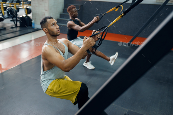 Two athletes at exercise machine, training in gym - Stock Photo - Images