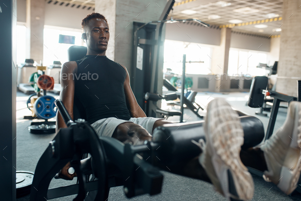 Muscular athlete in sportswear at exercise machine - Stock Photo - Images