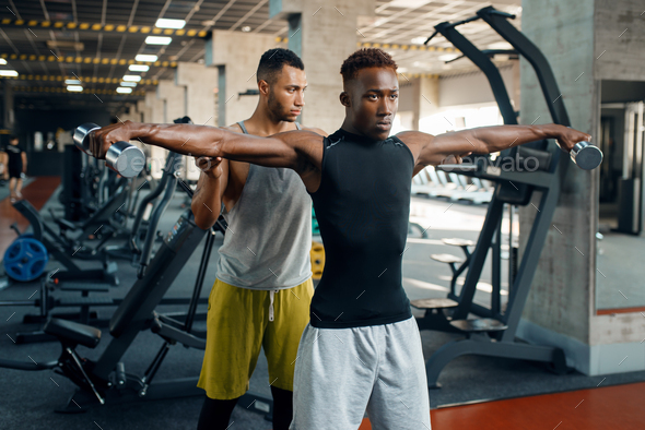 Two athletic men doing exercise with dumbbells - Stock Photo - Images
