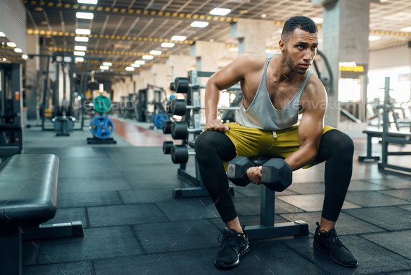 Muscular man doing exercise with heavy dumbbell - Stock Photo - Images