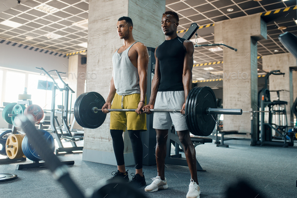 Two muscular men poses with heavy barbell in gym - Stock Photo - Images