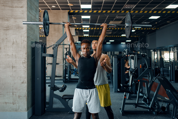 Athlete and his trainer, exercise with barbell - Stock Photo - Images