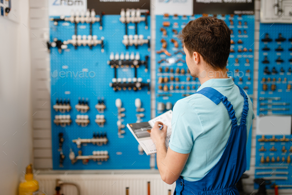 Plumber at showcase with valves and pipe equipment - Stock Photo - Images