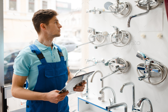 Plumber in uniform at showcase in plumbering store - Stock Photo - Images