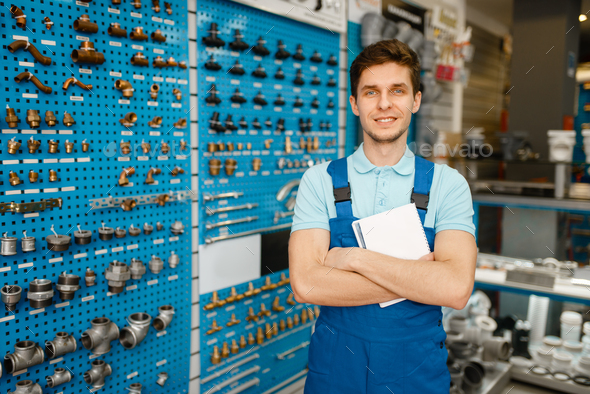 Plumber at showcase with valves and pipe adapters - Stock Photo - Images