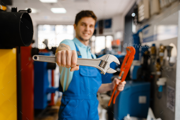 Plumber shows pipe wrenches in plumbering store - Stock Photo - Images