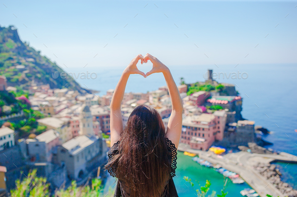Beautiful girl making with hands heart shape on the old coastal town background of Vernazza, Cinque - Stock Photo - Images