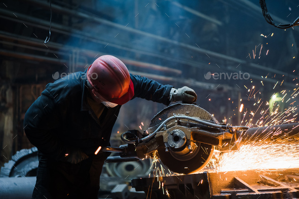 Employee grinding steel with sparks - focus on grinder. Steel factory - Stock Photo - Images