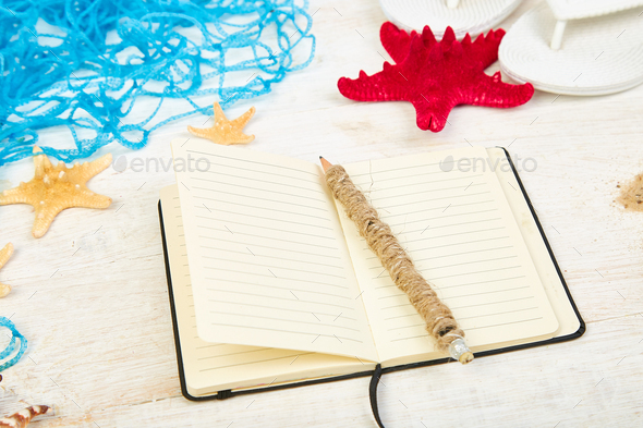Notebook, starfishes and seashells, glass with sand - Stock Photo - Images