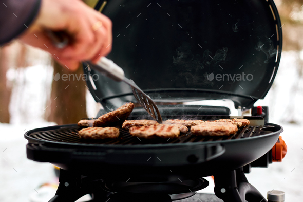 Man grilling steaks on a portable BBQ, Snowy winter barbecue - Stock Photo - Images