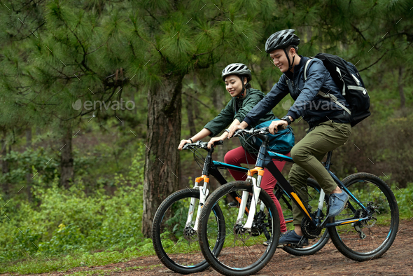Couple cycling through forest - Stock Photo - Images