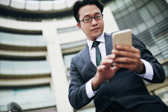 Businessman texting on smartphone - Stock Photo - Images