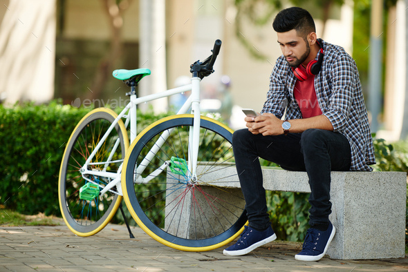 Handsome Cyclist Using Smartphone - Stock Photo - Images