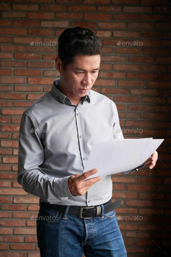Asian Businessman Studying Documents - Stock Photo - Images