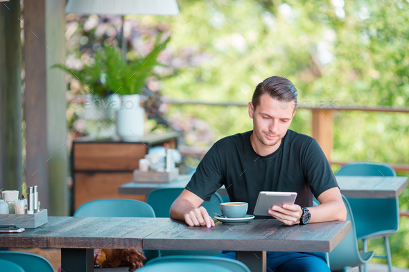 Young man with laptop in outdoor cafe drinking coffee. Man using mobile smartphone - Stock Photo - Images