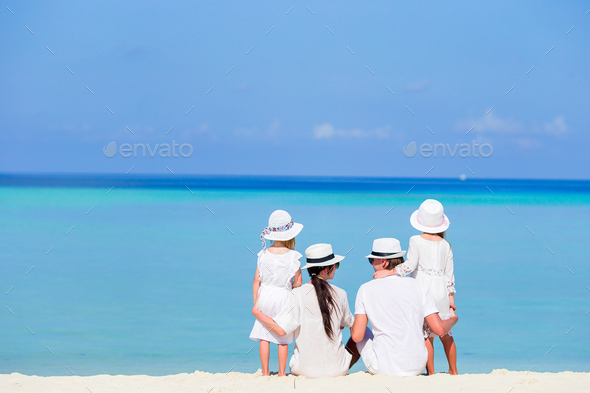 Back view of a happy family on tropical beach - Stock Photo - Images