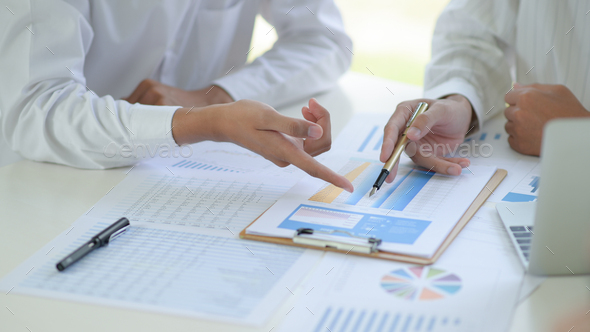 Two business teams discuss and analyze the graphs of project working together in office. - Stock Photo - Images
