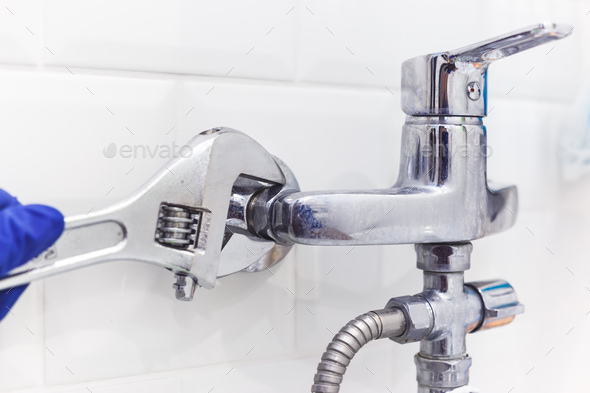 Plumber uses pipe wrench for service shower mixer tap - Stock Photo - Images
