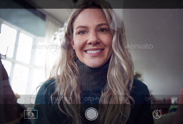 View From Behind Mobile Phone Screen As Woman Takes Selfie At Home - Stock Photo - Images